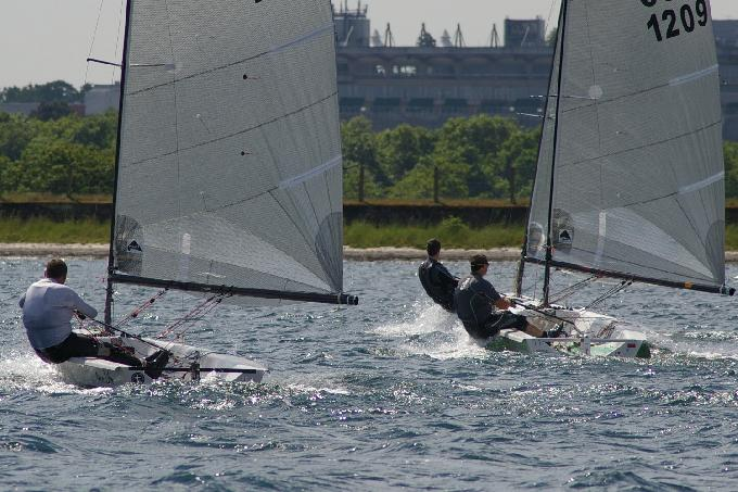 Sandown Park racecourse in the background as sailors battle down the reach at the IBRSC Phantom Open 2013.JPG